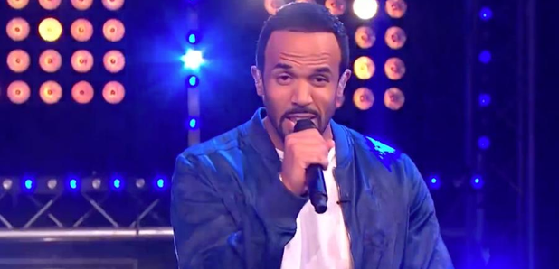 Craig David holding microphone on stage