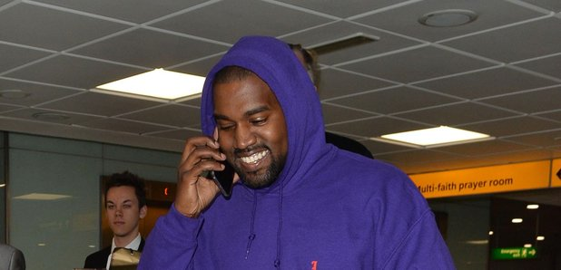 Kanye West shares a rare smile at London Heathrow